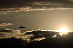 Plane Flying into Sunset Stock Photography
