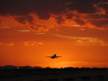 Plane Flying into the Sunset Stock Image
