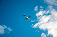The plane is flying to cloud  blue sky from ariport among sunlig. The plane is flying to cloud  blue sky from airport among sunlight Royalty Free Stock Image