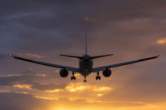 Plane flying towards the runway during a cloudy sunrise. Stock Photos