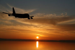 Plane flying towards sunset Royalty Free Stock Images