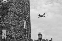 Plane flying by the town of Windsor b/w Royalty Free Stock Photos