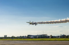 Plane flying upside down. Stunt aircraft flying upside down over the ground leaves smoke trail at the Bucharest Air Show on June 22, 2014 in Bucharest, Romania Royalty Free Stock Photo