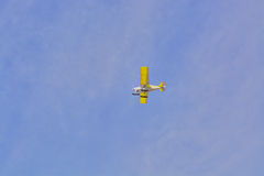 The plane is flying yellow against the blue sky with clouds Royalty Free Stock Images