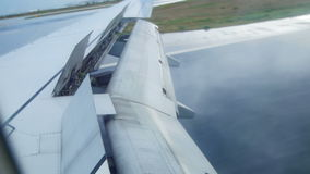 The plane goes on landing, it lands, smoke comes from under the shasi, a view from the airplane window, the wing of the stock footage