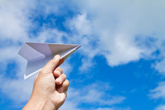 Plane in hand. Hand with paper plane against blue sky Royalty Free Stock Images