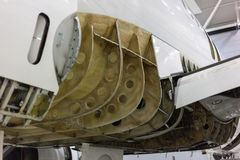 Plane in hangar. Aircraft repair in hangar. Opened fuselage Stock Photo