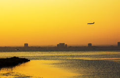 Plane on the horizon during sunset by the sea Royalty Free Stock Image
