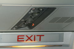 Plane Interior. The interior of an aeroplane, personal controls for comfort and an exit sign for safety Royalty Free Stock Photos