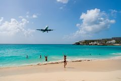Plane land over people on beach of philipsburg, sint maarten. Jet flight low fly over blue sea. Airplane in cloudy blue sky. Beach. Vacation at Caribbean royalty free stock photography