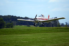Plane Landing. Piper landing in a green field with pilot unidentified Stock Photo