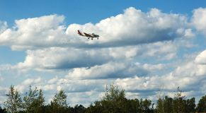 Plane Landing. Plane coming in for a landing with a cloudy sky behind it Stock Photo