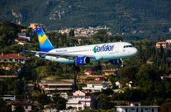 Plane landing. Corfu, Greece - August 18, 2015: Thomas Cook Condor Airbus A320-200 landing on runway of Corfu International Airport Royalty Free Stock Photo
