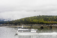 Plane Landing Over Ferry in Alaska Stock Photography