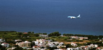 Plane is landing over suburbs towards sea. Royalty Free Stock Images