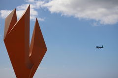 Plane landing and sculpture sitting Stock Images