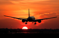 Plane landing in sunrise Stock Image