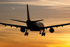Plane landing in sunrise Stock Photos