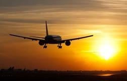Plane landing in sunrise Stock Images