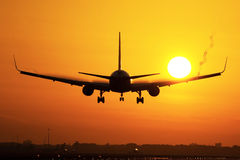 Plane landing in sunrise Royalty Free Stock Images