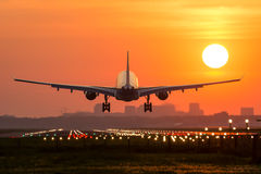 Plane is landing during sunrise. Royalty Free Stock Images