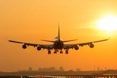 Plane is landing during sunrise. Huge Airplane is landing during a nice morning sunrise. Close up Stock Image