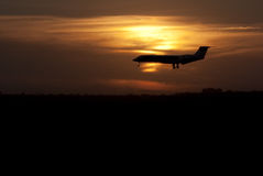 Plane landing at sunset. Airplane landing in silhouette against a glowing setting sun Stock Photos