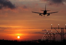 Plane landing in a sunset. Back light Stock Photos