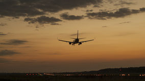Plane landing in a sunset Stock Images