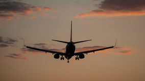 Plane landing in a sunset Royalty Free Stock Photo