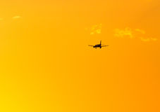 The plane is landing at sunset. The plane is landing at the yellow sunset stock images