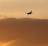 The plane is landing at sunset Royalty Free Stock Image