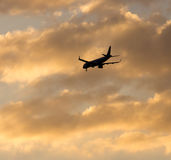 The plane is landing at sunset. The plane is landing at the yellow sunset royalty free stock images