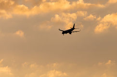 The plane is landing at sunset. The plane is landing at the yellow sunset royalty free stock image