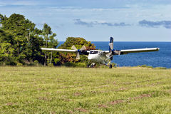Plane landing on tropical island by sea Royalty Free Stock Images