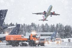 The plane lands at the airport during a snowfall. Snowplow cleans the airfield stock photo