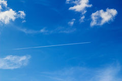 Plane leaving white lines against the blue sky. Royalty Free Stock Image