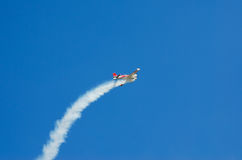 The plane left in the trail of smoke in the blue sky.  Royalty Free Stock Photography