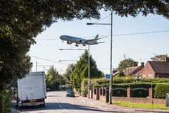 Plane low approach above houses Stock Images