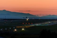 The plane makes landing on the runway at night royalty free stock images