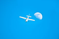 A plane beside the moon Royalty Free Stock Photo