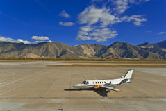 Plane and mountains. Small jet airplane on a tarmac in front of a mountain range Stock Images