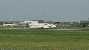 Lufthansa planes taxiing in Munich Airport, spring. Plane movement in Munich Airport MUC. green grass stock footage