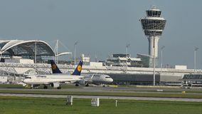 Lufthansa planes taxiing in Munich Airport, spring. Plane movement in Munich Airport MUC. green grass stock video footage
