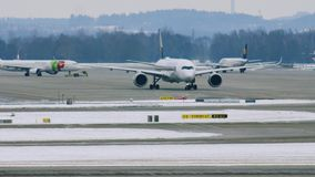 Airport movement in Munich Airport MUC. Plane movement in Munich Airport MUC. Winter weather conditions with snow on runways stock video footage