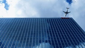 Plane Over Building. Plane flies over mirrored building Stock Images