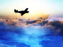 Plane Over The Clouds 3. A plane flying over a abstract starry cloud and sun scene Stock Photo
