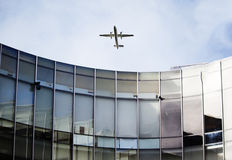 Plane over curved building Stock Photography