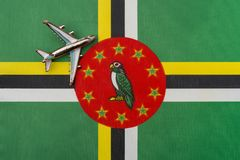 Plane over the flag of Dominica concept of travel and tourism. Toy plane on the flag in the background royalty free stock photo