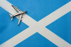 Plane over the flag of Scotland the concept of a travel. Toy plane on the flag in the background royalty free illustration